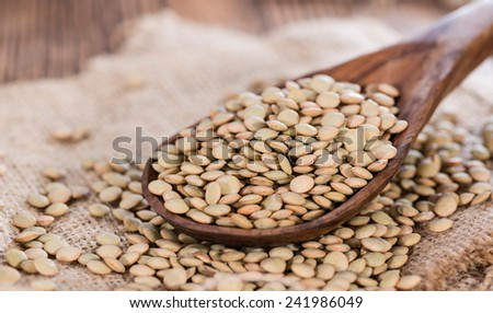 Brown Lentils (detailed close-up shot) on rustic wooden background  - stock photo