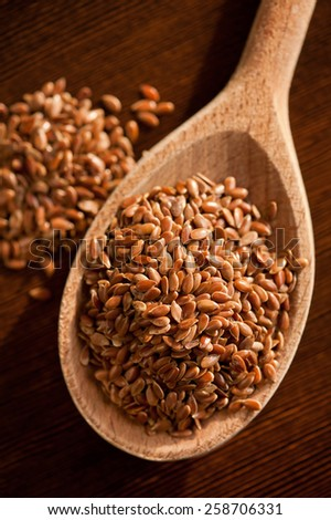 Brown linseeds portion on wooden spoon closeup, healthy raw flax seeds heap in day light, vertical orientation, nobody. - stock photo