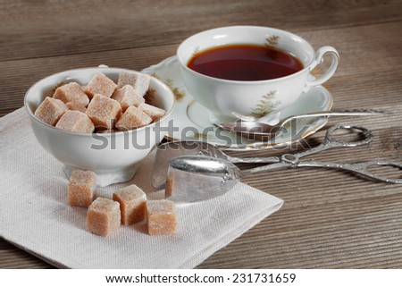 Brown lump sugar and a cup of tea - stock photo