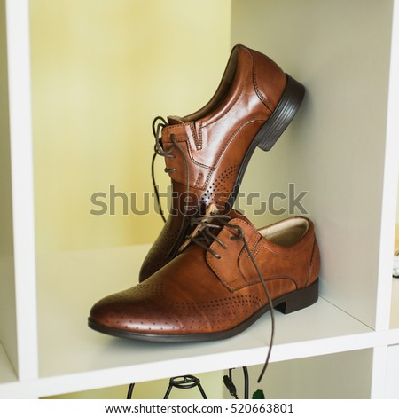 Brown man's shoes stand on a shelf. Men's style, fashion. Charges groom.