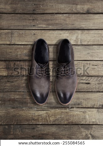 Brown men's shoes on a wooden background - stock photo
