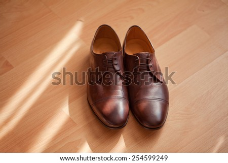 Brown men's shoes. Sunlight. - stock photo