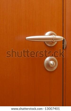 Brown modern wooden door with the golden handle - stock photo