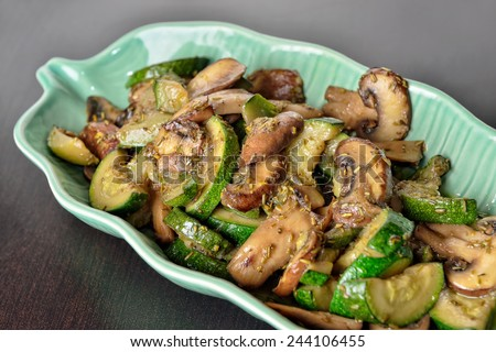 Brown mushrooms fried with zucchini, pepper and rosemary - stock photo