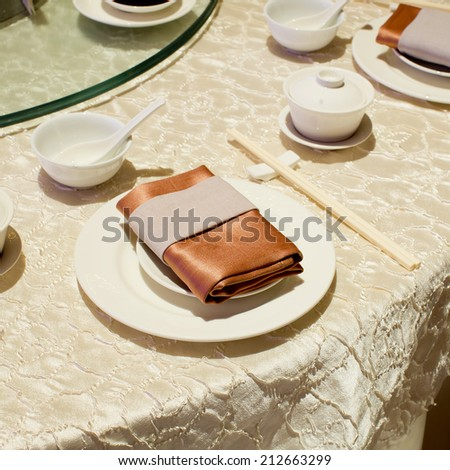 Brown napkin on blank plates, empty cup, soup bowl, spoon and chop stick on dinner table