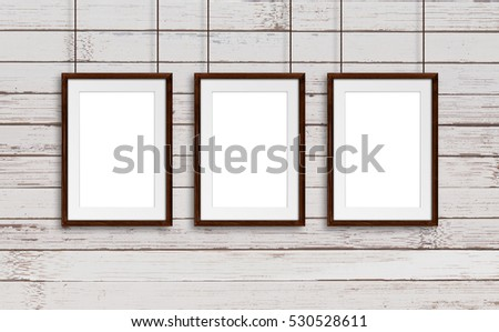 brown natural wooden frames hanging on cords against old panels background retro style