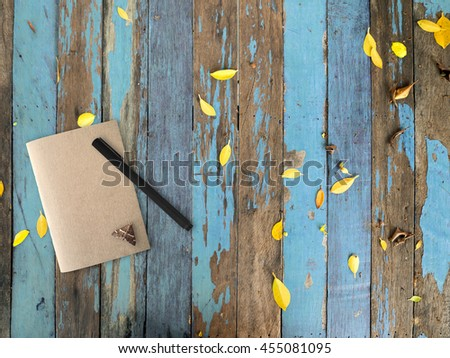 Brown note book with a tiny moth on table. - stock photo