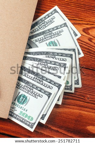 Brown notebook with dollars and pen lying on wooden table with place for text - stock photo