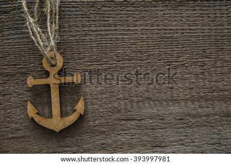 brown or gray  wooden anchor on the background of wooden board. empty copy space for inscription. - stock photo