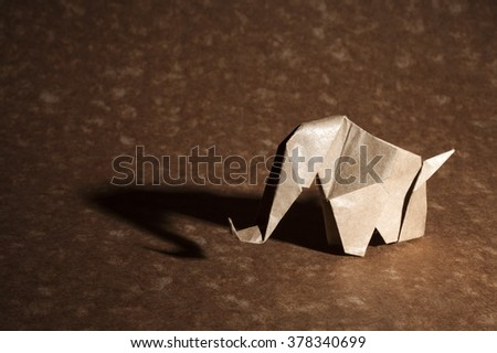 Brown origami elephant isolated on craft paper background. - stock photo