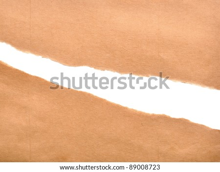 Brown package paper torn to reveal white panel ideal for copy space - stock photo