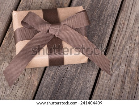 Brown package with ribbon and bow on wooden boards - stock photo
