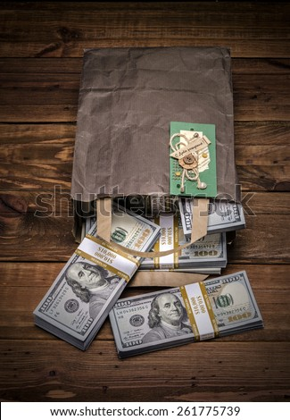 Brown paper bag containing that moolah and Congratulation card. Bag full of money - vintage photography of brown paper bag with stacks of hundred dollar bills on wooden background - stock photo