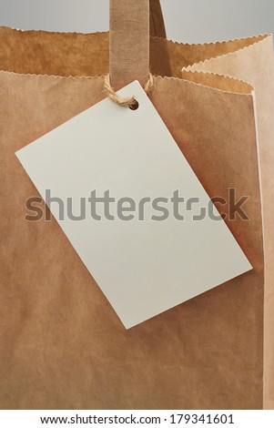 Brown paper bag with blank tag attached for your personal message or company branding - stock photo