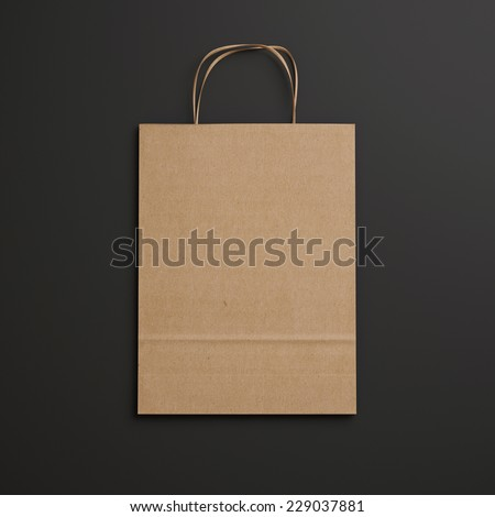 Brown paper bag with handles on black background - stock photo