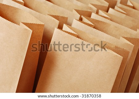 Brown paper bags in rows with tilted composition.  Macro with shallow dof. - stock photo