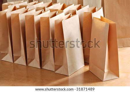 Brown paper bags on wooden table in morning sunlight. - stock photo
