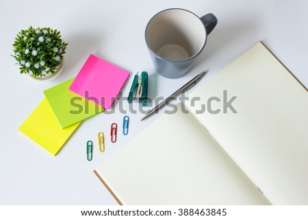 brown paper blank and paper note, color pencil, cup, pen on white desk with copyspace / for your text or message, artwork / view from above, top view / business, office supplies concept - stock photo