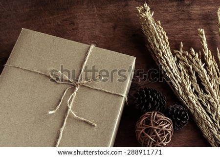 Brown paper box on old wood background with dried flower, Vintage tone - stock photo