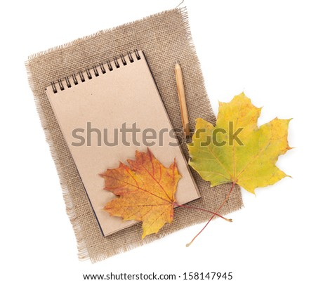 Brown paper notepad with pencil and autumn leaf over burlap. Isolated on white background - stock photo