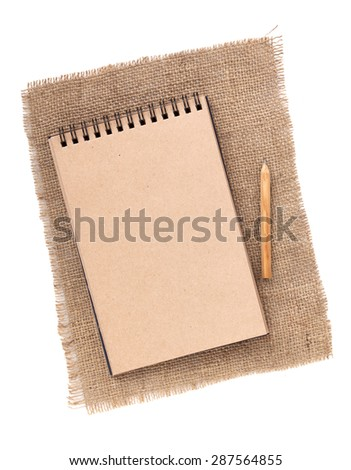 Brown paper notepad with pencil over burlap. Isolated on white background - stock photo