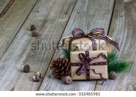 Brown paper packages tied in purple ribbon by acorns, pine cone and green garland on antique rustic wooden background - stock photo
