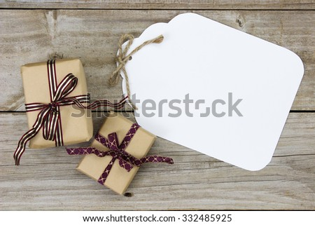 Brown paper packages tied in ribbon by blank gift tag on antique rustic wooden background; above view - stock photo