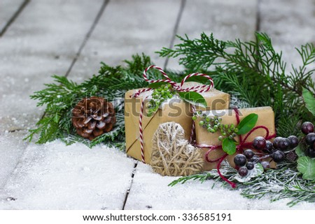 Brown paper packages tied up in string, Christmas tree garland, rope heart and snow on antique rustic wooden background - stock photo