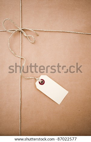 Brown paper parcel with a blank tag and copy space - stock photo