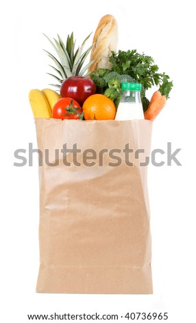 Brown paper shopping bag filled with fresh fruit and vegetables - stock photo