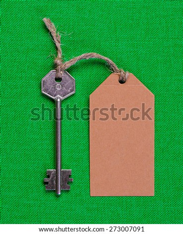 brown paper tag attached to the metal silver key on the green  fabric background - stock photo