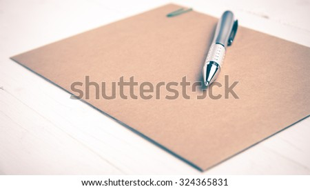 brown paper with pen on white table vintage style