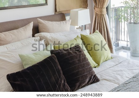 brown pillows and green pillows on bed in bedroom at home