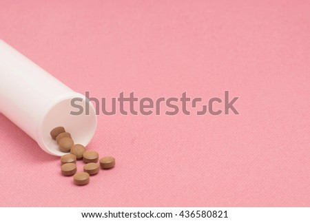 Brown pills with pill bottle on pink background. Room for text on right. Selective focusing. - stock photo