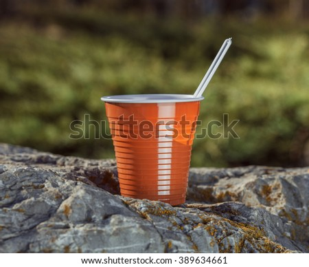 brown plastic coffee cup with a spoon on a rock on a background of forest landscape. - stock photo