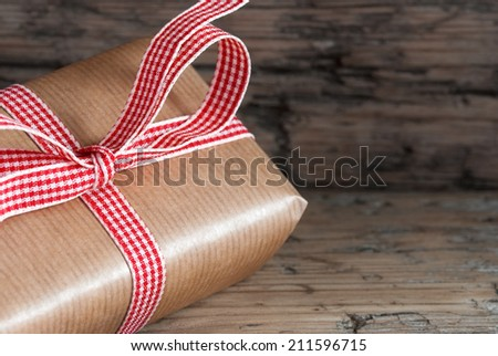 Brown Present on Wooden Background with Copy Space - stock photo