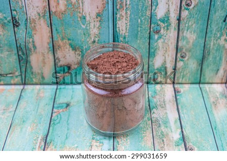 Brown pure cocoa powder in a mason jar over rustic wooden background - stock photo