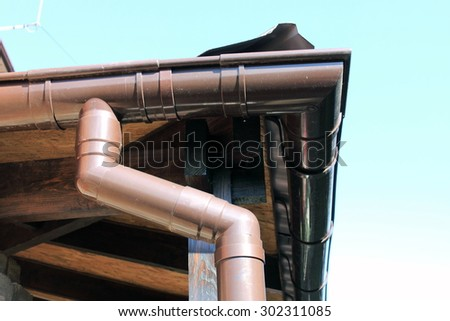 brown rain gutter on a home against blue sky - stock photo