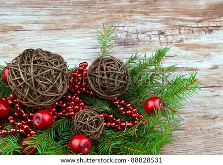 Brown rattan christmas balls with fresh spruce branch on old wooden background - stock photo