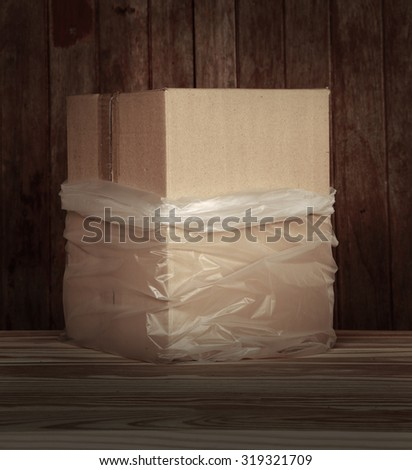 Brown recycle paper box in plastic bag lay down on wood floor and grunge wood panel as still life art with plenty room for copy - stock photo