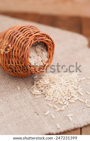 Brown rice in a wicker jug on sacking - stock photo