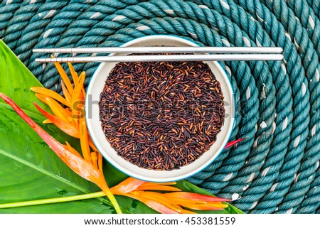 Brown rice in bowl with chopsticks and flower