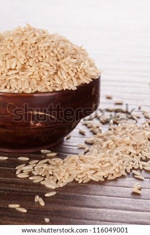 Brown rice in brown wooden round oriental bowl on brown background. Asian rice eating concept. - stock photo