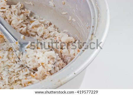 Brown rice in electric rice cooker isolated on a white background