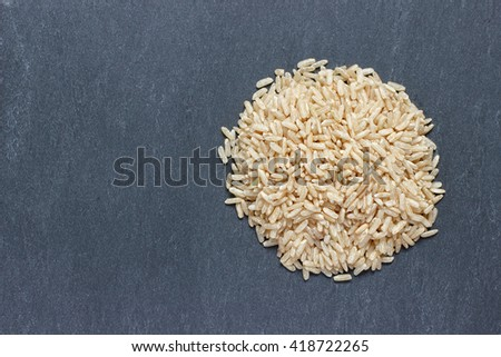 Brown rice on natural dark background