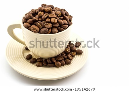 Brown roasted coffee beans in coffee cup on white background.