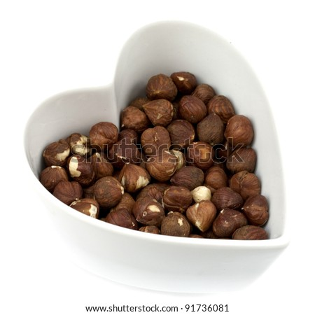 Brown roasted hazelnuts in a heart shaped bowl isolated on white