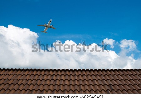 brown roof tiles in front of airplane in the sky background