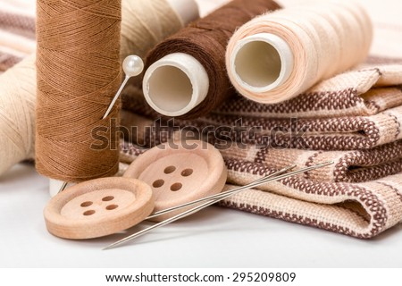Brown sewing kit: buttons, needles, threads and materials
