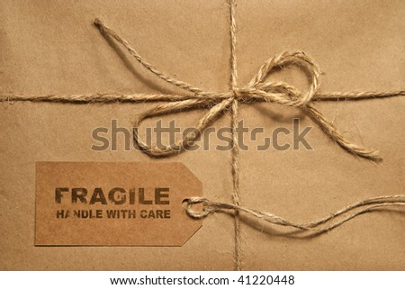 Brown shipping parcel tied with twine and a blank shipping tag for copy space - stock photo